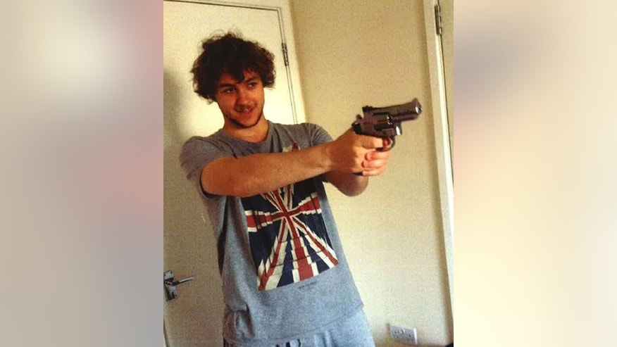 "This undated handout photo provided by the Metropolitan Police shows Damon Smith holding a ball-bearing gun. A jury on Wednesday, May 3, 2017 has found a university student with an interest in weapons and extremism guilty of planting a home-made bomb on a busy London subway train. Damon Smith, 20, faces years in jail after building the device at home with a 2-pound ($2.58) clock from Tesco after googling an al-Qaida article entitled ""Make a bomb in the kitchen of your mom."" (Metropolitan Police via AP)"