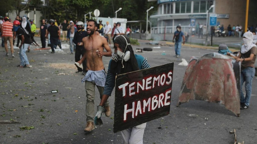 "A demonstrator holds a sign the reads in Spanish ""We are hungry"" during clashes with the Bolivarian National Guard, at El Hatillo municipality outside Caracas, Venezuela, Tuesday, May 2, 2017. People blocked streets in Caracas with broken concrete, twisted metal and flaming piles of trash to protest the president's bid to rewrite the constitution amid a rapidly escalating political crisis.(AP Photo/Fernando Llano)"