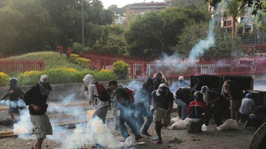 Demonstrators clash with the Bolivarian National Guard, at El Hatillo municipality outside Caracas, Venezuela, Tuesday, May 2, 2017. People blocked streets in Caracas with broken concrete, twisted metal and flaming piles of trash to protest the president's bid to rewrite the constitution amid a rapidly escalating political crisis.(AP Photo/Fernando Llano)