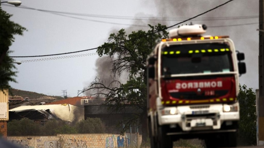 A firefighter truck leaves as smoke rises from a factory after several explosions, in Arganda del Rey, outside Madrid, Thursday, May 4, 2017. A fire and several explosions ripped through an industrial waste treatment factory Thursday in a town near Madrid, sending 30 people to the hospital for treatment and forcing the immediate evacuation of nearby schools and offices, officials said. (AP Photo/Francisco Seco)