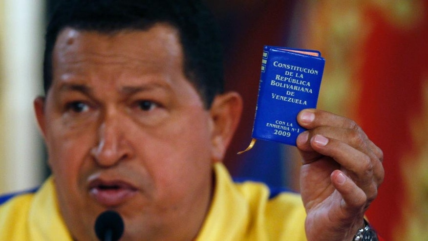 FILE - In this Sept. 27, 2010 file photo, Venezuela's President Hugo Chavez holds up a miniature copy of the constitution during a press conference at Miraflores presidential palace in Caracas, Venezuela. Chavez's first order of business as president was to rework the old constitution. The results were packaged into a tiny blue book that became one of the most iconic visual symbols of his revolution. (AP Photo/Fernando Llano, File)