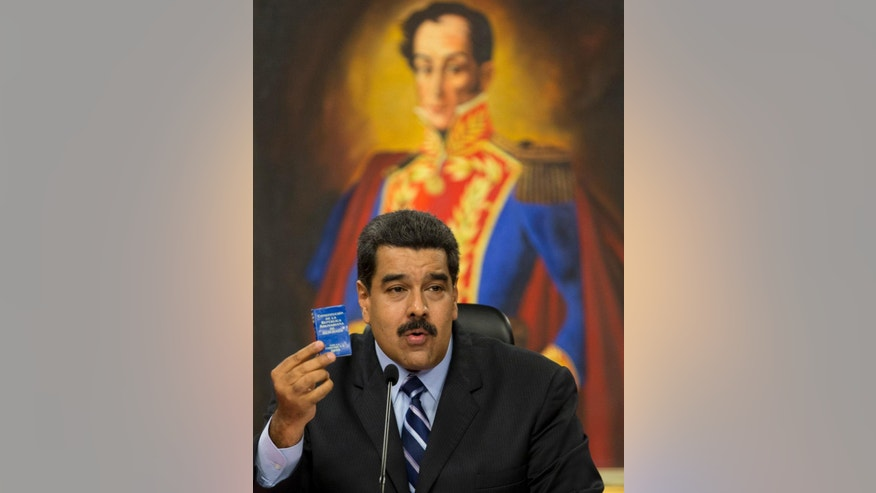 "FILE - In this May 17, 2016 file photo, Venezuela's President Nicolas Maduro holds up Venezuela's constitution packaged into a tiny blue book, during a press conference at Miraflores presidential palace in Caracas, Venezuela. Hardly a day passes without Maduro or some other government official appearing in public and waving the document, which has become the Venezuelan version of the late Chinese communist leader Mao Zedong's ""little red book."" (AP Photo/Ariana Cubillos, File)"