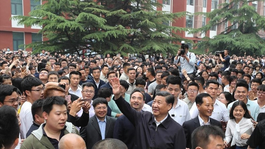 In this Wednesday, May 3, 2017 photo released by Xinhua News Agency, Chinese President Xi Jinping, center, waves to teachers and students as he visits the China University of Political Science and Law in Beijing. Xi has discussed North Korea during a phone call with Philippine President Rodrigo Duterte, who referred to Beijing's important role in promoting peace on the Korean Peninsula. (Ding Lin/Xinhua via AP)