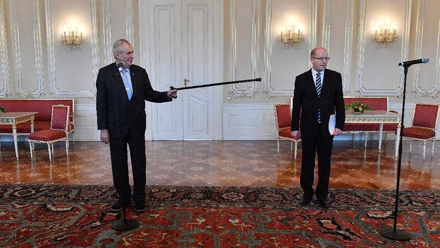Czech President Milos Zeman, left, points his stick as Czech Prime Minister Bohuslav Sobotka prior to their meeting in Prague on Thurday, May 4, 2017. Sobotka arrived at Prague Castle, the seat of the presidency, on Thursday for consultations with the president following his decision to resign with his government over the business dealings of his finance minister. (Michal Dolezal/CTK via AP)