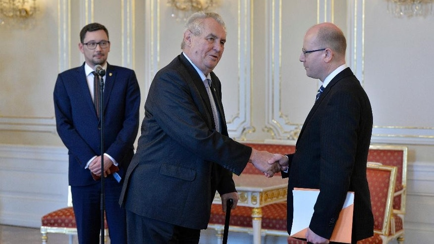 Czech President Milos Zeman, center, and Czech Prime Minister Bohuslav Sobotka shake hands prior to their meeting as president's spokesman Jiri Ovcacek, left, watches them in Prague on Thursday, May 4, 2017. Sobotka arrived at Prague Castle, the seat of the presidency, on Thursday for consultations with the president following his decision to resign with his government over the business dealings of his finance minister. (Michal Dolezal/CTK via AP)