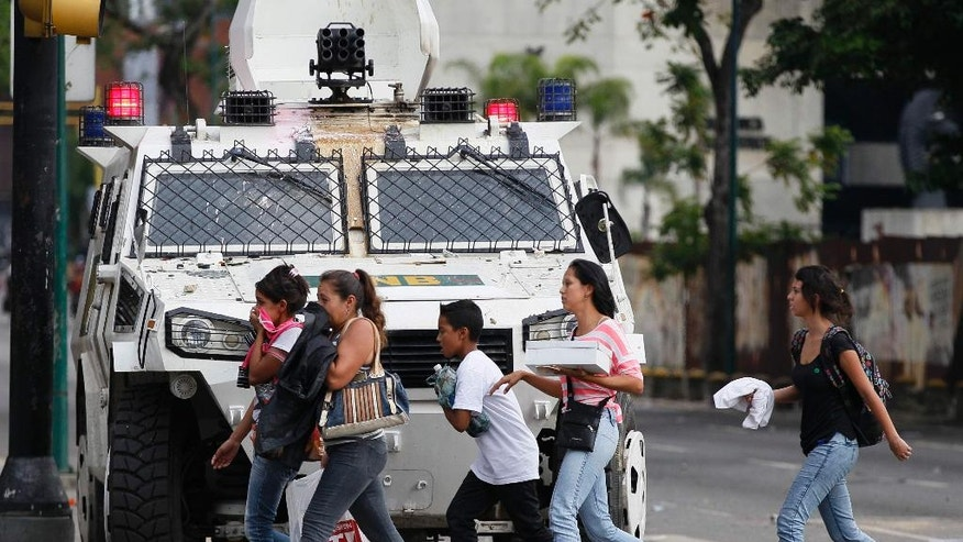 People cover their faces from teargas as they walk past an armored car of the National Guard in Caracas, Venezuela, Wednesday, May 3, 2017. Driving the latest outrage is a decree by Venezuelan President Nicolas Maduro to begin the process of rewriting Venezuela's constitution, which was pushed through in 1999 by his predecessor and mentor, the late President Hugo Chavez. (AP Photo/Ariana Cubillos)