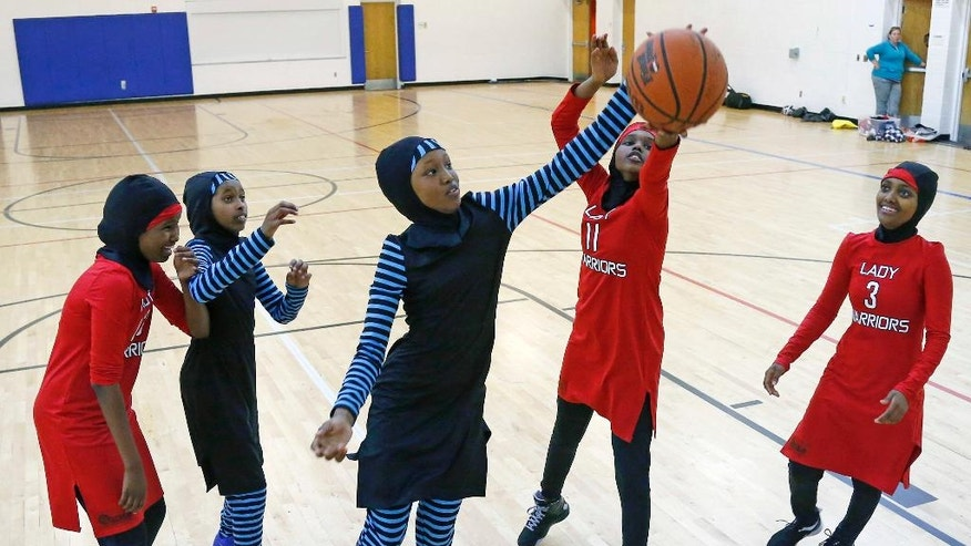 FILE - In this June 16, 2015, file photo, East African Muslim girls practice basketball in their new uniforms in Minneapolis. Members of basketball's international governing body are expected to vote to eliminate a rule that bans religious headgear during competition. The vote could come during a meeting on Thursday or Friday, May 5, 2017. Headgear was banned for safety reasons two decades ago out of fear it could fall off, causing a player to slip or become entangled. (AP Photo/Jim Mone, File)