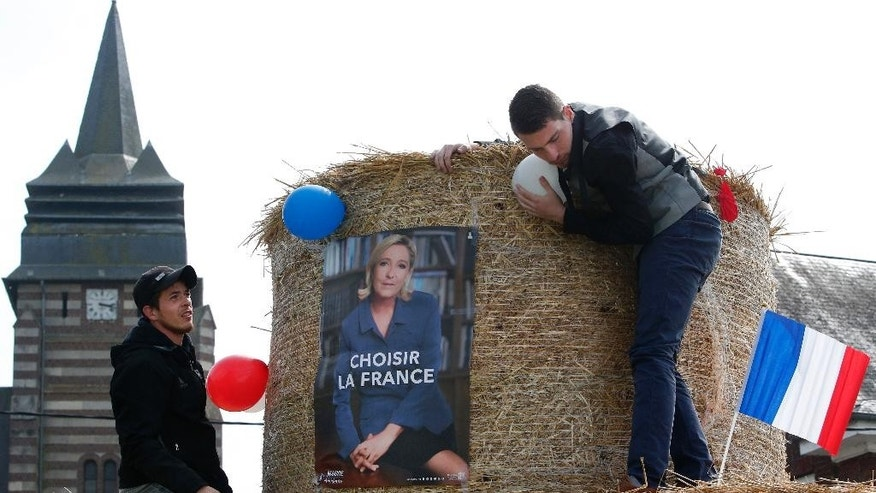 "Two young men put up decorations ahead of the visit of French far-right leader and presidential candidate Marine Le Pen in Ennemain, northern France, Thursday, May 4, 2017. Le Pen's election poster reads ""Choose France"". (AP Photo/Michel Spingler)"