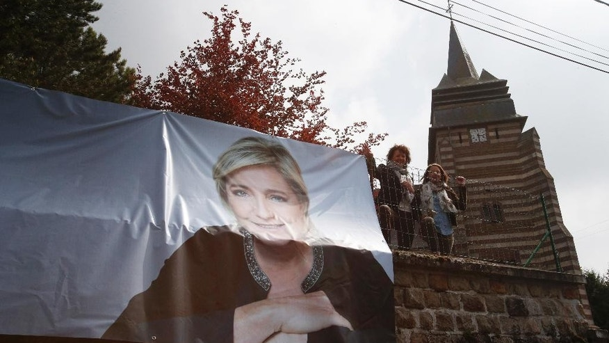 Supporters of far-right presidential candidate Marine le Pen wait for her near a portrait of the candidate in Ennemain, northern France, Thursday, May 4, 2017. Le Pen and centrist candidate Emmanuel Macron face on in Sunday's runoff vote, with the latest polls suggesting Macron is well ahead. (AP Photo/Michel Spingler)
