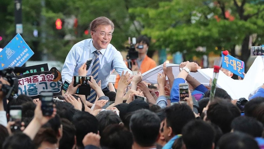 FILE - In this Thursday, May 4, 2017 file photo, South Korean presidential candidate Moon Jae-in of the Democratic Party greets supporters during an election campaign in Goyang, South Korea. For South Koreans living next door to a hostile, nuclear-armed state that regularly threatens their annihilation, their vote in Tuesday's presidential election likely will be based in part on each candidate's plan for how to handle North Korea. The North Korea conundrum is a perpetual foreign policy headache for South Korea's leaders and one that is impacting the presidential race in several ways. (AP Photo/Lee Jin-man, File)