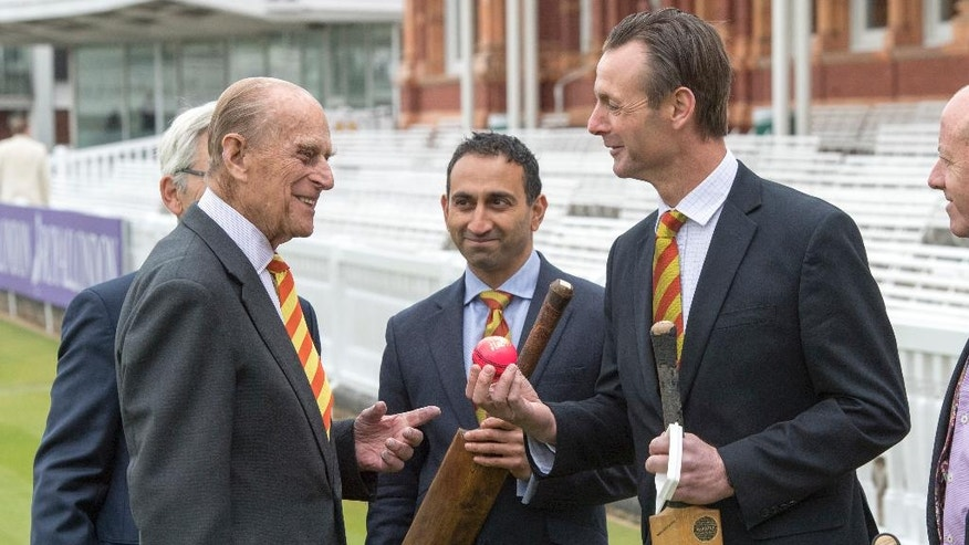 FILE - In this Wednesday, May 3, 2017 file photo former England cricketer John Stephenson, right, shows Britain's Prince Philip, the Duke of Edinburgh, a pink cricket ball, during his visit to Lord's Cricket Ground to open the new Warner Stand, in London. Buckingham Palace said Thursday May 4, 2017 that Prince Philip will no longer carry out engagements starting this fall.  (Arthur Edward/Pool Photo via AP)