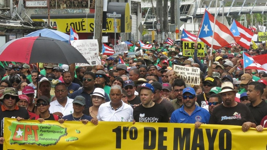 Singer Rene Perez, of Calle 13, front row, third from right, joins a protest against looming austerity measures amid an economic crisis during the May Day march, as protesters demand an audit to identify those responsible for the public debt, in San Juan, Puerto Rico, Monday, May 1, 2017. Puerto Rico is preparing to cut public employee benefits, increase tax revenue, hike water rates and privatize government operations, among other things. (AP Photo/Danica Coto)