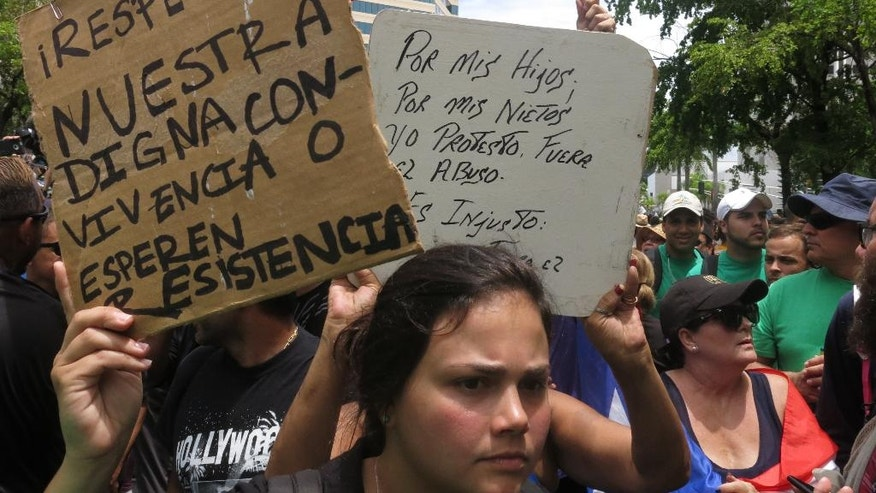 "People protest looming austerity measures amid an economic crisis and demand an audit on the island's debt to identify those responsible, during the May Day march in San Juan, Puerto Rico, Monday, May 1, 2017. The signs read in Spanish, left, ""Respect our dignified coexistence or expect resistance,"" and ""For my children, for my grandchildren, I protest. Stop the abuse."" (AP Photo/Danica Coto)"