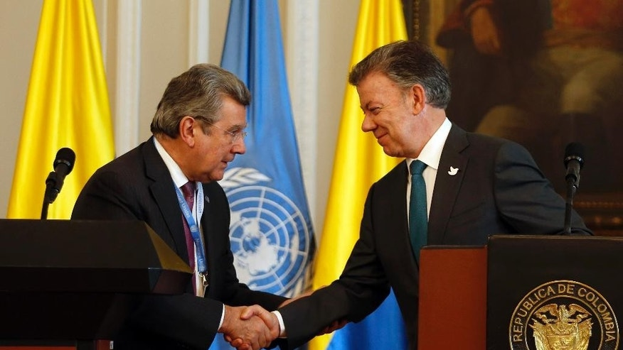 Colombia's President Juan Manuel Santos, right, shakes hands with Ambassador Elbio Rosselli, Permanent Representative of Uruguay to the United Nations, after a joint statement at the presidential palace in Bogota, Colombia, Thursday, May 4, 2017. Ambassadors for the nations on the U.N. Security Council met with Santos as they evaluate the role international peacekeepers are playing in the demobilization of leftist rebels. (AP Photo/Fernando Vergara)