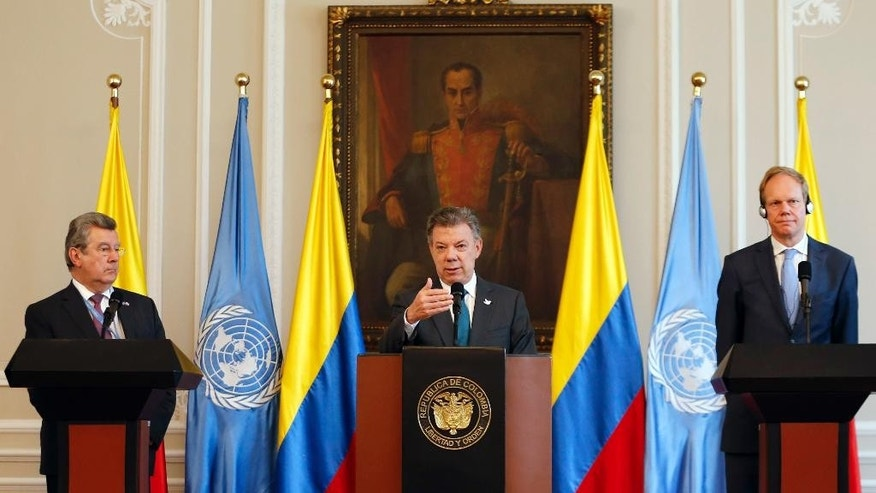 Colombia's President Juan Manuel Santos, center, speaks during a joint statement with Ambassadors Elbio Rosselli, permanent representative of Uruguay to the United Nations, left, and Matthew Rycroft, permanent representative of Britain to the United Nations, at the presidential palace in Bogota, Colombia, Thursday, May, 4, 2017. Ambassadors for the nations on the U.N. Security Council met with Santos as they evaluate the role international peacekeepers are playing in the demobilization of leftist rebels. (AP Photo/Fernando Vergara)