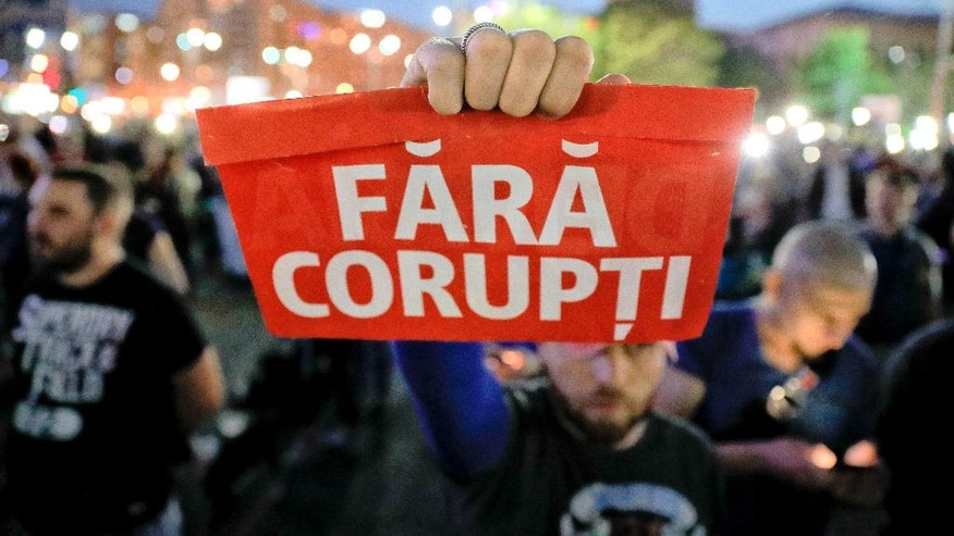"A man holds a poster that reads ""Without Corruption"" during a protest in Bucharest, Romania, Wednesday, May 3, 2017. Over one thousand people have gathered outside the government offices shortly after a parliamentary legal committee approved a draft that would grant an amnesty to people convicted of bribery and influence peddling, months after massive anti-graft protests.(AP Photo/Vadim Ghirda)"