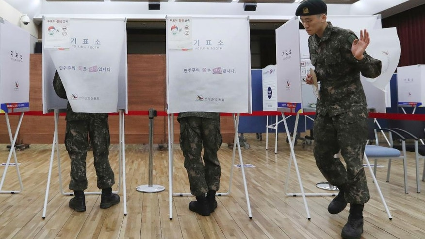 A South Korean soldier exits a polling booth to cast his early vote for the May 9 presidential election at a local polling station in Seoul, South Korea, Thursday, May 4, 2017. South Korea's presidential election is scheduled for May 9, 2017. (AP Photo/Lee Jin-man)