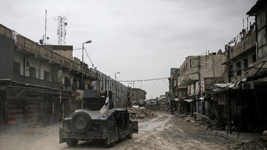 In this Tuesday, May 2, 2017 photo, a humvee of the Iraqi Federal Police drives through an abandoned street in western Mosul, Iraq. The spokesman for the ministry of defense said Thursday, May 4, 2017, that Iraqi forces have begun a push along the northern edge of Mosul's western half where Islamic State group fighters are holding onto a cluster of neighborhoods. The front lines in western Mosul have inched forward for months as IS fighters have used a claustrophobic battle space and hundreds of thousands of civilians as human shields to slow Iraqi troops. (AP Photo/Bram Janssen)