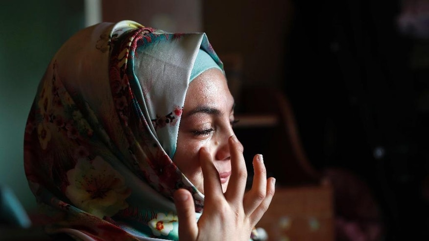 In this picture taken on Thursday, April 27, 2017, Alaa, 19, who was shot in March 2013 in her jaw and other several injuries on her body during clashes between Syrian government forces and the rebels in the al-Waer neighborhood in the Syrian province of Homs, wipes tears as she tells her injury story, at her home in Bebnine town, north Lebanon. (AP Photo/Hussein Malla)