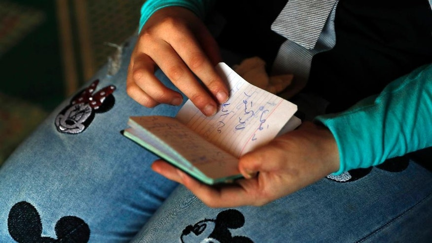 "In this picture taken on Thursday, April 27, 2017, Alaa, 19, who was shot in March 2013 in her jaw and other several injuries on her body during clashes between the Syrian government forces and the rebels at al-Waer neighborhood in the Syrian province of Homs, shows a small book where she wrote to her mother when her tongue was stitched up with an Arabic words reading: ""Call the doctor, I can't sleep from the saliva,"" as she tells her injury story at her home in Bebnine town, north Lebanon. (AP Photo/Hussein Malla)"