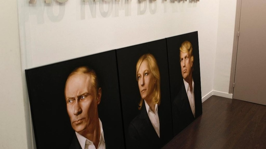 A painting made by an unidentified Russian artist shows Russian President Vladimir Putin, left, French far-right candidate for the presidential elections Marine le Pen and U.S President Donald Trump, at Le Pen's campaign headquarters, Friday, May 5, 2017 in Paris. Inscription reads; In the name of People. (AP Photo/Laurent Rebours)