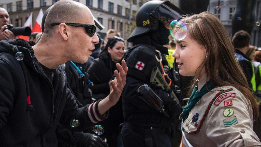 "FILE - In this file photo dated  Monday, May 1, 2017, taken in Brno, Czech Republic, showing 16-year-old Lucie Myslikova talks to a protester at a right wing demonstration. The Czech teenager was among some 300 protesters who confronted a rally of the far right Workers Party of Social Justice on May Day in the second largest Czech city of Brno.  Myslikova said it is important for young people to comment on public issues, ""I think it makes sense to be seen and to be heard,"" Myslikova told The Associated Press in an interview Friday May 5, 2017, after becoming an internet sensation because of this photo of her confronting a rally of the far-right Workers Party of Social Justice on May Day.(AP Photo/Vladimir Cicmanec, FILE)"