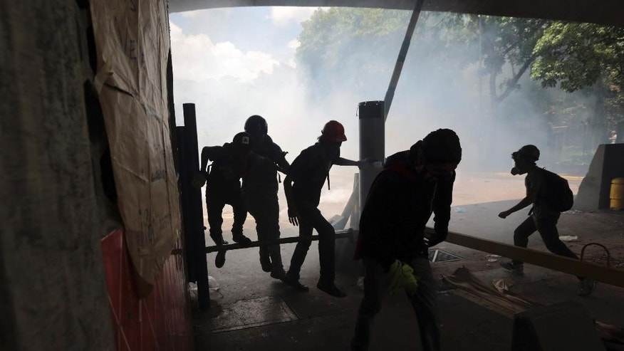 Students run from tear gas fired by National Police outside the Central University of Venezuela in Caracas, Thursday, May 4, 2017. Students held demonstrations across Caracas Thursday as a two-month-old protest movement that shows no signs of letting up claimed more lives. (AP Photo/Fernando Llano)