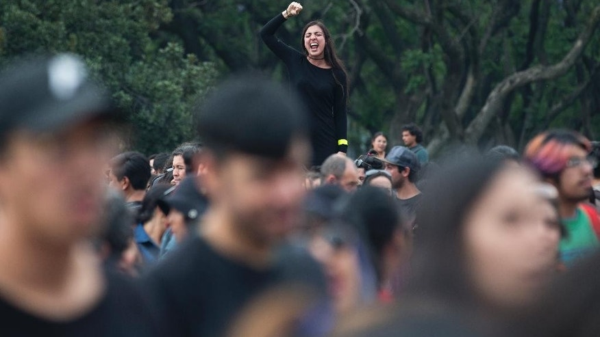 A woman shouts political slogans during a march at Mexico's National Autonomous University (UNAM) after a woman was found dead on campus in Mexico City, Friday, May 5, 2017. The woman's body was found on May 3 tied to a phone booth in the gardens next to UNAM's engineering school, according to a university statement. Her identity and cause of death were not immediately known. (AP Photo/Eduardo Verdugo)