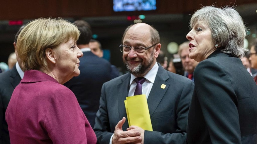 FILE - In this Dec. 15, 2016 file photo German Chancellor Angela Merkel, left, speaks with British Prime Minister Theresa May, right, and then European Parliament President Martin Schulz, center, during a round table meeting at an EU Summit in Brussels. A pair of upcoming German state elections could show whether the center-left Social Democrats can win back the momentum they need to deny conservative Chancellor Angela Merkel a fourth term. Sunday's vote in Schleswig-Holstein and the May 14 election in North Rhine-Westphalia, Germany's most populous state, are the last tests at the ballot box before a national election in September.  (AP Photo/Geert Vanden Wijngaert, file)