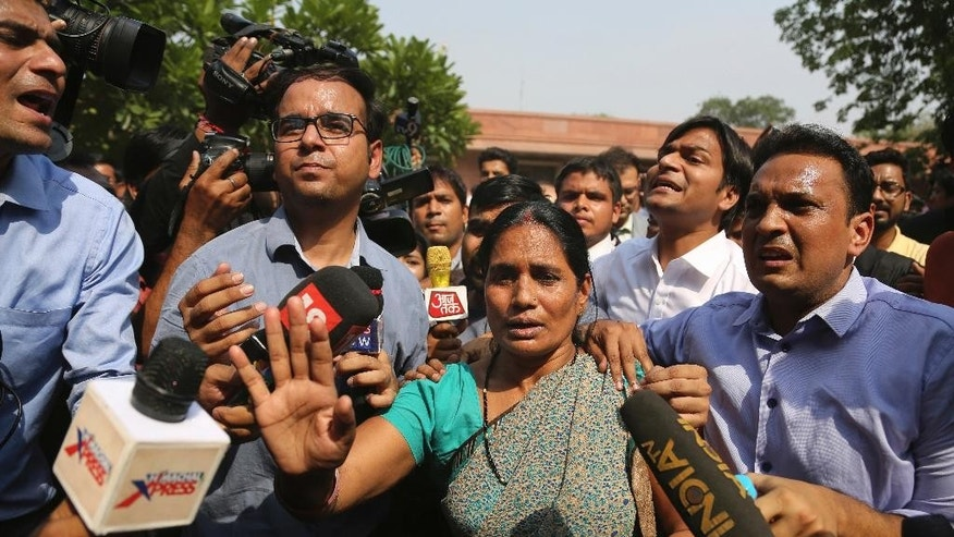 Journalists crowd around Asha Devi, mother of the victim of the fatal 2012 gang rape on a moving bus, after the Supreme Court verdict in the case, in New Delhi, India, Friday, May 5, 2017. India's top court on Friday upheld the death sentences of four men who were convicted in the fatal gang-rape and torture of a 23-year-old medical student on a moving bus in the Indian capital nearly five years ago. (AP Photo/Altaf Qadri)
