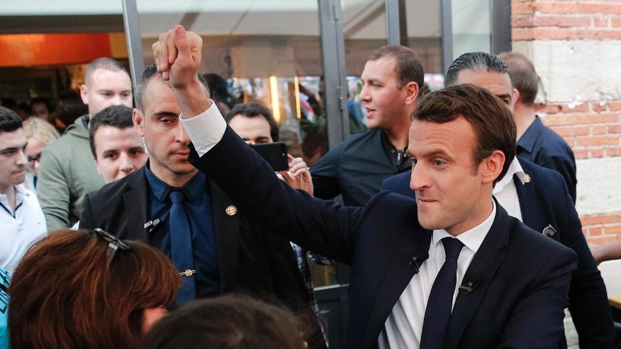 French independent centrist presidential candidate Emmanuel Macron, right, shakes hands with supporters during a campaign rally in Albi, southern France, Thursday, May 4, 2017. The 39-year-old independent candidate faces far-right National Front leader Marine Le Pen in Sunday's presidential runoff. (AP Photo/Christophe Ena)