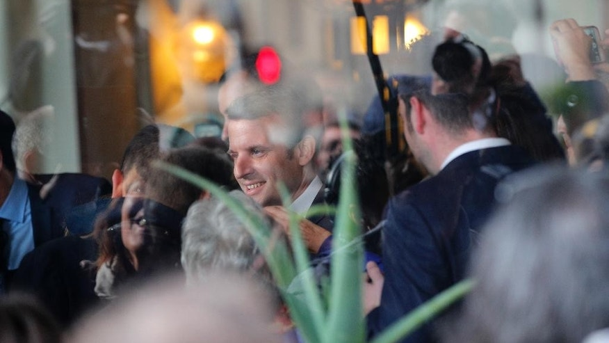 French independent centrist presidential candidate Emmanuel Macron, center, smiles in his hotelin Rodez, southern France, Friday, May 5, 2017. The 39-year-old independent candidate faces far-right National Front leader Marine Le Pen in Sunday's presidential runoff. (AP Photo/Christophe Ena)