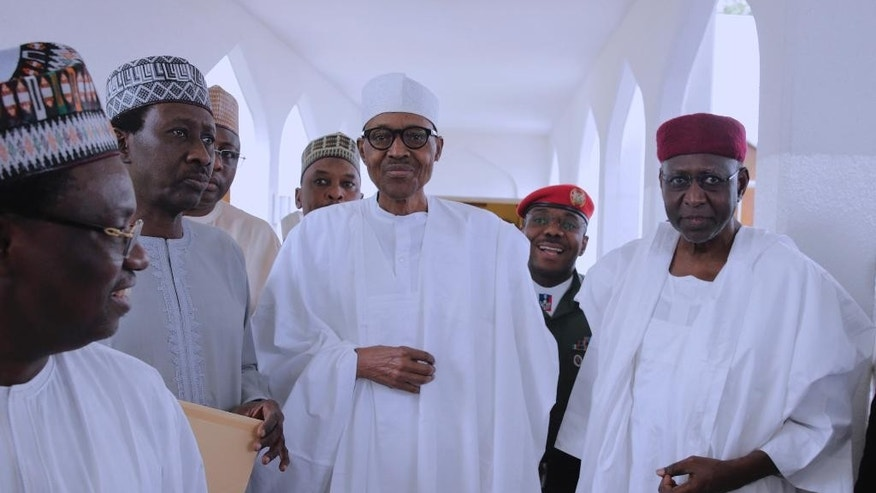 In this photo released by the Nigeria State House, Nigeria's President Muhammadu Buhari, centre, with government officials after Friday prayers at the presidential palace in Abuja, Nigeria, Friday, May. 5, 2017.  Nigeria's 74-year old president has emerged to attend Friday prayers after missing a number of public engagements and three straight weekly cabinet meetings because of poor health.  (Sunday Aghaeze/Nigeria State House via AP)