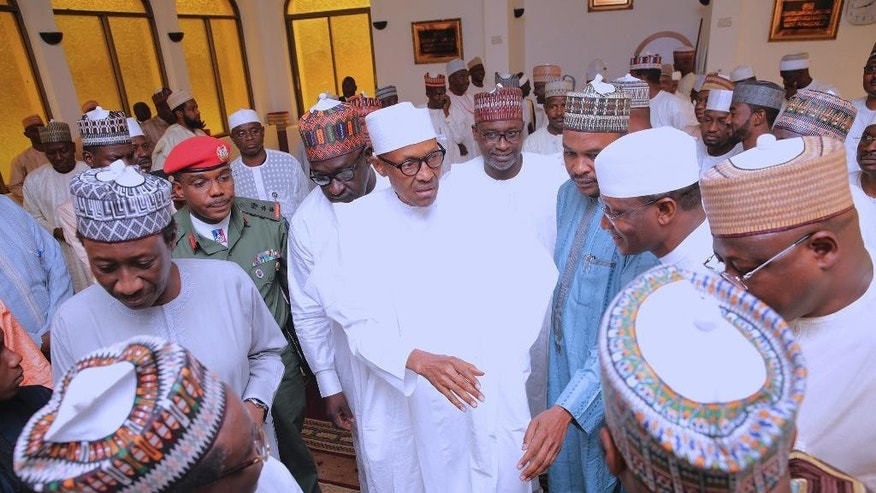 In this photo released by the Nigeria State House, Nigeria's President Muhammadu Buhari, centre, greets government officials after Friday prayers at the presidential palace in Abuja, Nigeria, Friday, May 5, 2017.  Nigeria's 74-year old president has emerged to attend Friday prayers after missing a number of public engagements and three straight weekly cabinet meetings because of poor health.   (Sunday Aghaeze/Nigeria State House via AP)