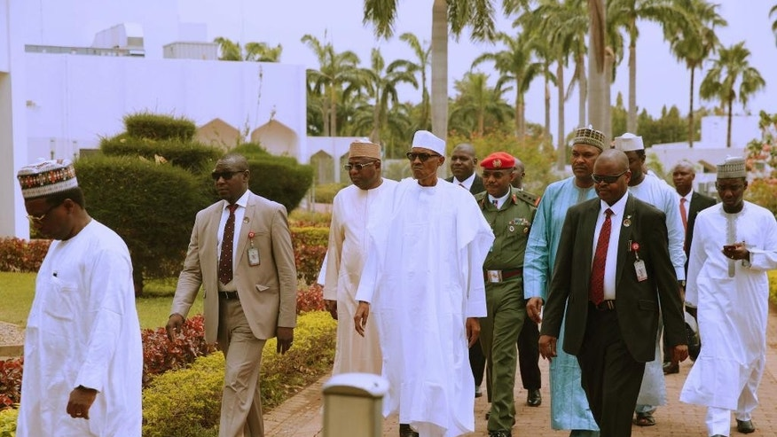 In this photo released by the Nigeria State House, Nigeria's President Muhammadu Buhari, centre, arrives for Friday prayers at the presidential palace in Abuja, Nigeria, Friday, May. 5, 2017.  Nigeria's 74-year old president has emerged to attend Friday prayers after missing a number of public engagements and three straight weekly cabinet meetings because of poor health.   (Sunday Aghaeze/Nigeria State House via AP)