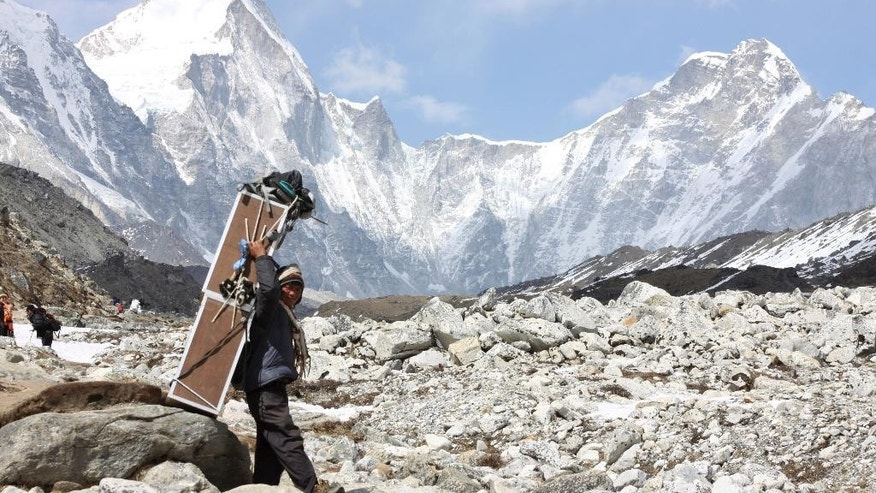 FILE - In this Friday, April 10, 2015, file photo, a porter carries crates containing oxygen tanks, with Mt Lingtren seen behind left, and Mt. Khumbutse, right, on his way towards Everest Base Camp, at Lobuche, Nepal. A Nepalese official says Sherpa workers are fixing the final route to the summit of Mount Everest and the first climb of the season could be days away.  (AP Photo/Tashi Sherpa, File)