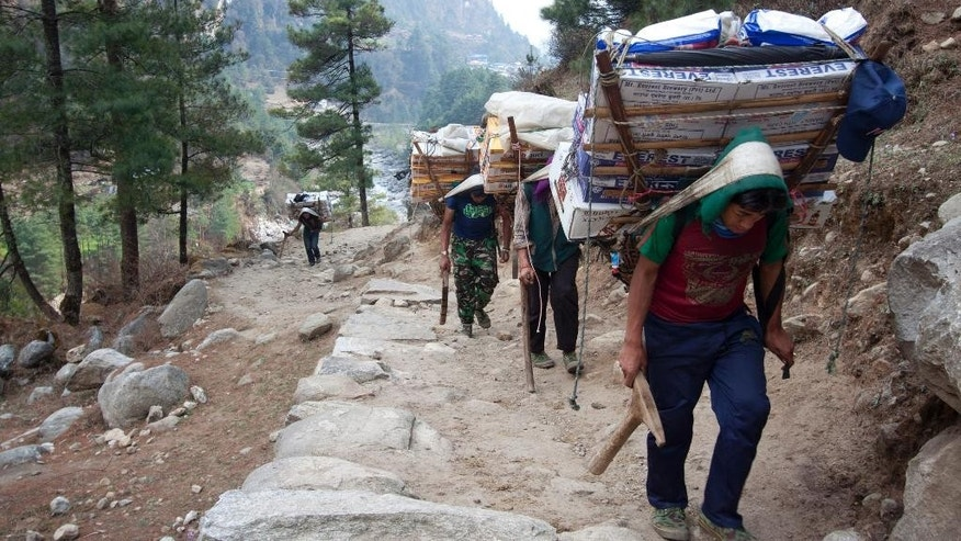 FILE - In this Tuesday, March 24, 2015, file photo, porters with supplies for trekkers head towards Namche, in Zamphute, a village inhabited by mainly Sherpas, Nepal. TA Nepalese official says Sherpa workers are fixing the final route to the summit of Mount Everest and the first climb of the season could be days away. (AP Photo/Tashi Sherpa, File)