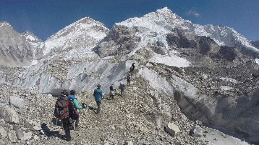 FILE - In this Feb. 22, 2016 file photo, international trekkers pass through a glacier at the Mount Everest base camp, Nepal. A Nepalese official says Sherpa workers are fixing the final route to the summit of Mount Everest and the first climb of the season could be days away. (AP Photo/Tashi Sherpa, file)