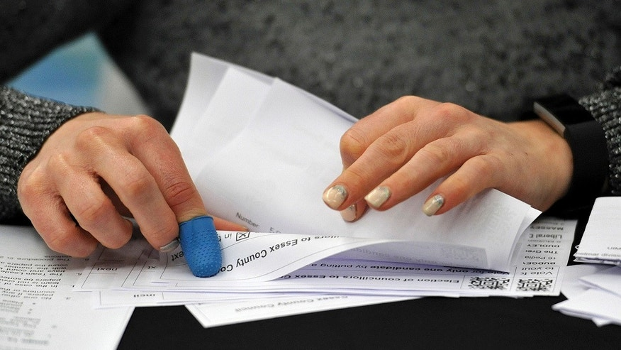 Election count staff tally ballot papers for the local election in Chelmsford, Britain, Thursday May 4, 2017. Theresa May's Conservatives have been projected to win a large number of the seats. (Nick Ansell/PA via AP)