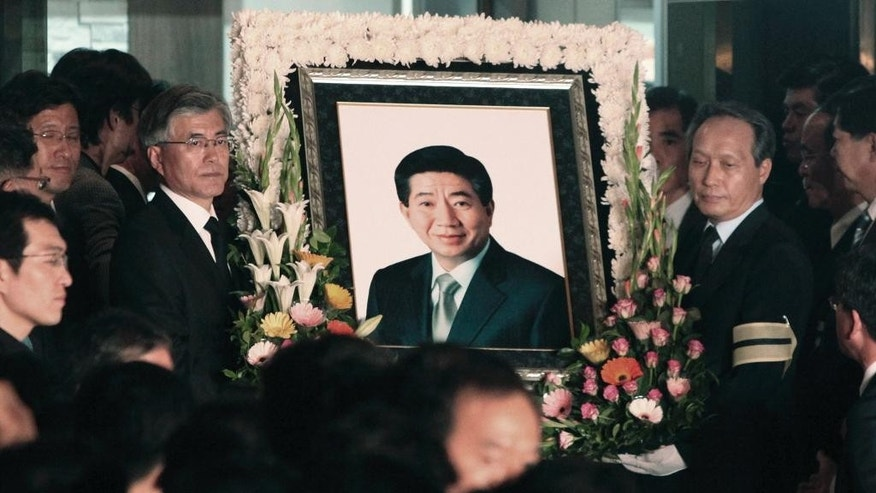 FILE - In this May 23, 2009 file photo, South Korean presidential candidate Moon Jae-in, second left, of the Democratic Party, carries a portrait of former South Korea President Roh Moo-hyun during Roh's funeral near the Roh's house in Gimhae, South Korea. Moon, chief of staff for a late liberal president, is forecast to win May 9 presidential election in South Korea. No understanding of Moon's career is complete without Roh, the darling of South Korean liberals who leapt to his death in 2009 amid a corruption scandal involving his family. Both started their careers as lawyers, with Moon joining Roh's law office in the 1980s. (AP Photo/Ahn Young-joon, File)