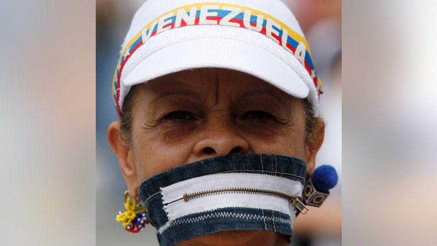 An anti-government protesters covers her mouth with a zipper during a women march against repression in Caracas, Venezuela, Saturday, May 6, 2017. Weeks of violent protests calling on President Nicolas Maduro to step down have left dozens of people dead. (AP Photo/Fernando Llano)