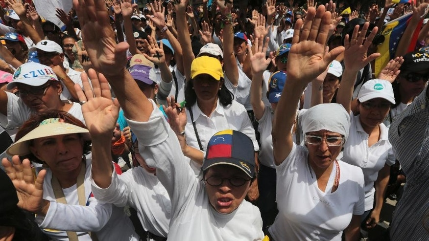Anti-government protesters raise their hands during a women march against repression and calling on President Nicolas Maduro to step down in Caracas, Venezuela, Saturday, May 6, 2017. Weeks of violent protests asking for Maduro's ouster have lefts dozens of people dead. (AP Photo/Fernando Llano)