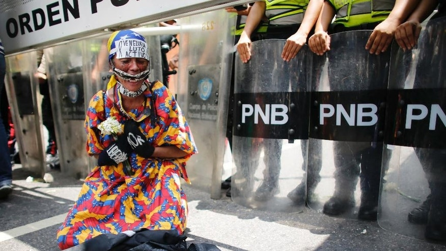 An anti-government wearing a Wayuu Indians dress kneels in front of riot police blocking a women march from reaching the Foreign Ministry in Caracas, Venezuela, Saturday, May 6, 2017. Thousands of women wearing white and carrying flowers marched to ask for a stop of repression and to pay tribute to those who were killed in weeks of demonstrations calling on President Nicolas Maduro to step down. (AP Photo/Ariana Cubillos)