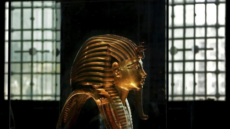 FILE -- In this Oct. 30, 2013 photo, the solid gold mask of King Tutankhamun is seen in its glass case, in the Egyptian Museum near Tahrir Square in Cairo, Egypt. Archaeologists and conservation experts met in Cairo on Sunday, May 7, 2017, to discuss the safe transportation of King Tutankhamun's throne, chests and bed from the Egyptian Museum in central Cairo to a new one being built on the other side of the city. Sunday's gathering brought together experts from Egypt, France, Spain, Germany, Switzerland, Denmark and Japan and is being organized by the Egyptian Ministry of Antiquities.  (AP Photo/Nariman El-Mofty)