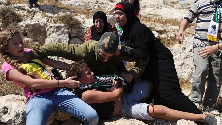 In this Friday, Aug, 28, 2015 file photo, Palestinian women and girls scuffle with an Israeli soldier trying to arrest a 12-year-old boy during a protest near the West Bank village of Nebi Saleh. Former Israeli combat soldiers who were thrust into the center of a diplomatic row between Israel and Germany, say the sudden international spotlight has given them a bigger platform to speak out against Israel's 50-year occupation of Palestinians.  (AP Photo, File)