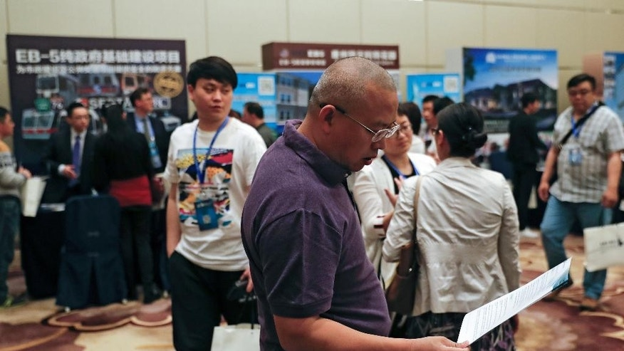 A Chinese man browses a leaflet as visitors seek information at the exhibitor booths in a Invest in America Summit, a day after an event promoting EB-5 investment in a Kushner Companies development held at a hotel in Beijing, Sunday, May 7, 2017. The sister of President Donald Trump's son-in-law Jared Kushner has been in China courting individual investors with a much-criticized federal visa program that provides a path toward obtaining U.S. green cards. (AP Photo/Andy Wong)