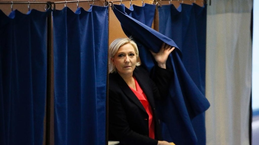 French far-right presidential candidate, Marine Le Pen exits a voting booth before casting her ballot in Henin Beaumont, France, Sunday, May 7, 2017. Voters across France are choosing a new president in an unusually tense and important election that could decide Europe's future, making a stark choice between pro-business progressive Emmanuel Macron and far-right populist Marine Le Pen. (AP Photo/Francois Mori)