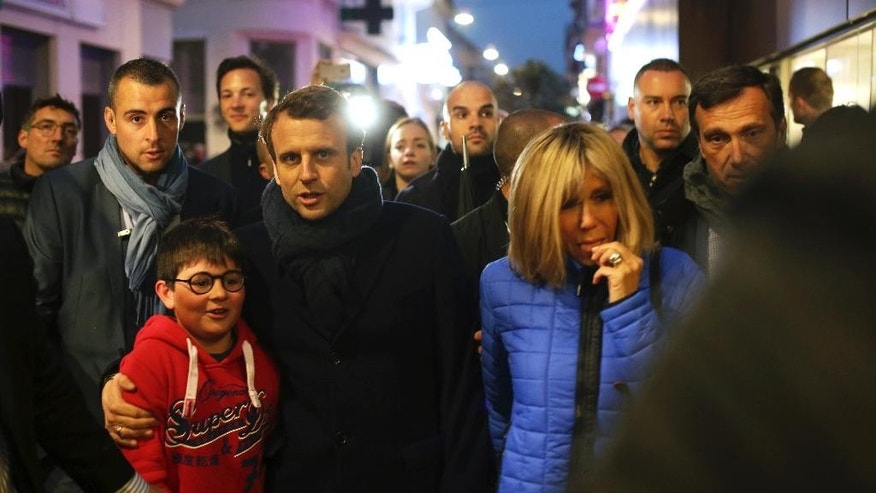 French independent centrist presidential candidate, Emmanuel Macron, center, and his wife Brigitte, right, walk in a street of Le Touquet, northern France, Saturday, May 6, 2017. Voting for France's next president has started in some overseas territories one day before voters in the mainland cast their ballots in Sunday's runoff between independent centrist Emmanuel Macron and far-right leader Marine Le Pen. (AP Photo/Thibault Camus)
