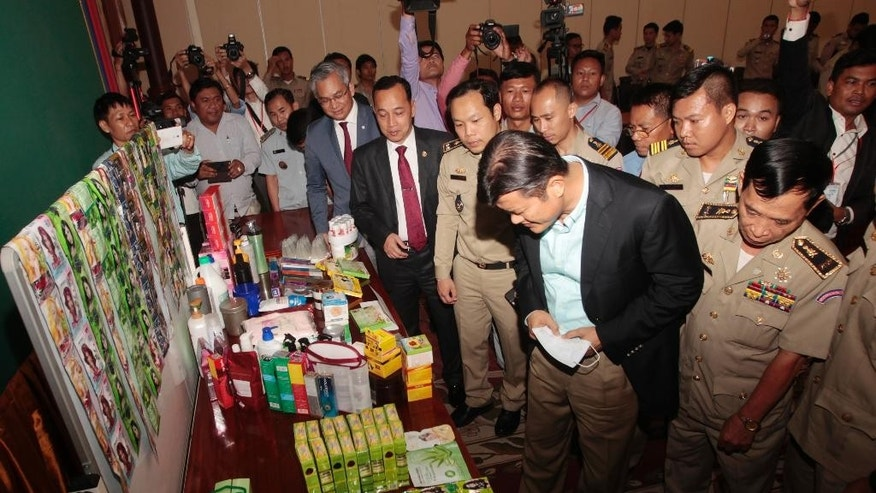 Cambodian government officials look at counterfeit cosmetics displayed during a press conference at Cambodia's Ministry of Interior in Phnom Penh, Cambodia, Monday, May 8, 2017. Cambodian authorities say they have confiscated nearly 70 tons of counterfeit cosmetics and raw materials for making them, a major haul that included imitations of South Korean, Thai, Japanese, Chinese and U.S. brands. (AP Photo/Heng Sinith)