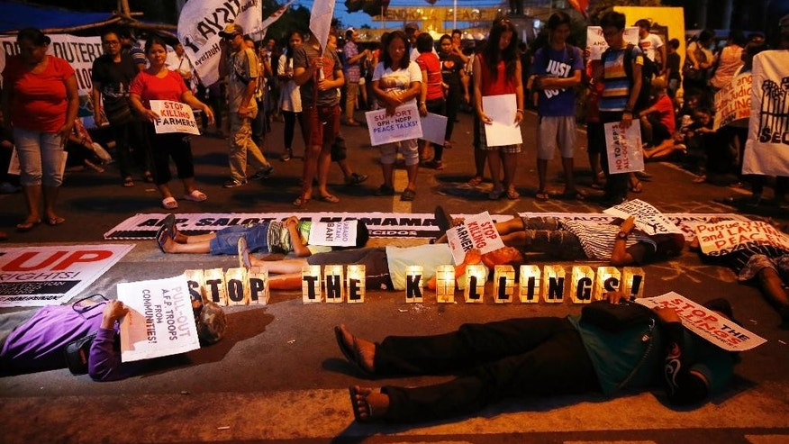 "Protesters stage a die-in during a rally near the Presidential Palace to protest the ""extrajudicial killings"" under President Rodrigo Duterte's so-called war on drugs which coincided with the U.N. Human Rights Council Universal Periodic Review in Geneva, Switzerland, Monday, May 8, 2017 in Manila, Philippines. Filipino Senator Alan Peter Cayetano briskly defended the human rights record of Duterte's government before the U.N. body in Geneva on Monday, saying his government always ""seeks to uphold the rule of law"" while critical Western nations aired concerns about deadly vigilante justice and extrajudicial killings in the country. (AP Photo/Bullit Marquez)"